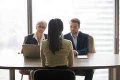 Achtermening van baan aanvragende besprekingen aan recruiters bij gesprek stock foto