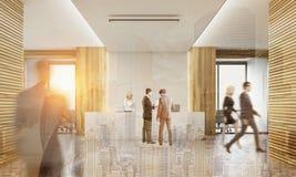 Achtermening van bedrijfsmensen in bureau met twee receptionnisten Stock Afbeeldingen
