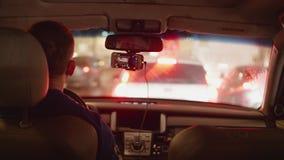 Achtermening van bestuurder in auto die zich in opstopping in avondstad bewegen stock footage
