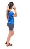 Achtermening van bevindende jonge mooie vrouw en het gebruiken van mobiel Royalty-vrije Stock Afbeelding