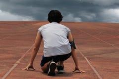 Achtermening van de atletenmens klaar om op spoor in het stadion tegen de donkere bewolkte achtergrond te lopen Stock Foto