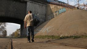 Achtermening van de dakloze mens die in stad lopen stock videobeelden
