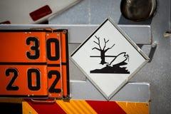 Achtermening van de dienst en bijtankende vrachtwagen op een luchthaven met GEVAARLIJK AAN AQUATISCH MILIEUwaarschuwingsbord royalty-vrije stock afbeeldingen