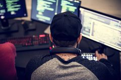 Achtermening van de getatoeeerde mens die aan het programma van de computercodage werken royalty-vrije stock fotografie