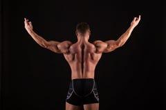 Achtermening van de gezonde spier jonge mens met zijn uitgerekte wapens uit geïsoleerd op zwarte achtergrond stock foto's