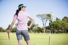 Achtermening van de golfclub van de vrouwenholding met hand op heup Royalty-vrije Stock Afbeeldingen