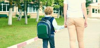 Achtermening van de hand van de moederholding van weinig zoon met rugzak in openlucht, terug naar school Royalty-vrije Stock Fotografie