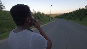 Achtermening van de jonge Afrikaans-Amerikaanse mens die onderaan de lege weg en de rokende sigaret bij zonsondergang lopen stock videobeelden
