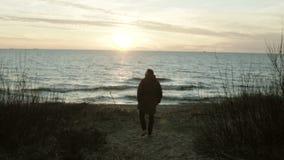Achtermening van de jonge mens die op de kust van het overzees op zonsondergang lopen Eenzame mannelijke het besteden tijd alleen stock footage