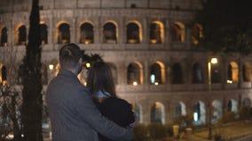 Achtermening van de jonge mens en vrouw die zich dichtbij Colosseum in Rome, Italië en samen het koesteren bevinden Royalty-vrije Stock Foto