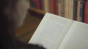 Achtermening van de jonge student die een boek in een bibliotheek dicht bestuderen Het meisje draait boekpagina die bevinden zich stock videobeelden