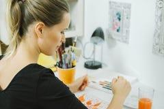 Achtermening van de Jonge vrouwelijke schets van de kunstenaarstekening op het haar werk stock fotografie