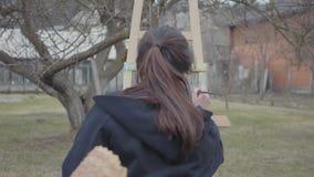 Achtermening van de jonge zitting van de meisjesschilder voor houten schildersezel die een beeld trekken Vrouwelijke kunstenaar i stock videobeelden