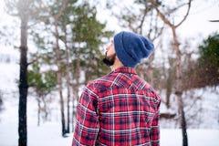 Achtermening van de knappe gebaarde jonge mens in rode van de plaidoverhemd en hoed vervanger in de winter sneeuwbos en het kijke stock foto
