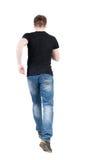 Achtermening van de lopende mens het lopen van kerel in motie stock foto