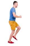 Achtermening van de lopende mens in t-shirt en borrels Stock Fotografie
