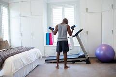 Achtermening van de mens die met domoren in slaapkamer uitoefenen Royalty-vrije Stock Foto