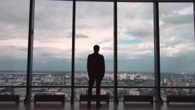 Achtermening van de mens in formele reeksen die zich voor panoramisch venster met stadsmening bevinden een mens bevindt zich voor stock video