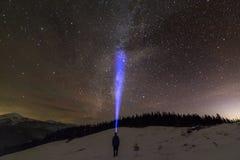Achtermening van de mens met hoofdflitslicht die op sneeuwvallei onder mooie donkerblauwe de winter sterrige hemel zich bevinden, stock afbeeldingen