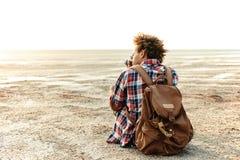 Achtermening van de mens met rugzak die foto's op strand nemen stock afbeelding