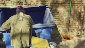 Achtermening van de oude dakloze mens die naar voedsel zoeken en voor recycling verpakken stock footage