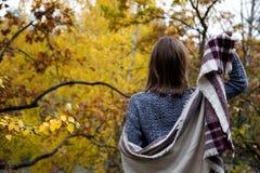 Achtermening van de rug van een meisje in een grijze kleding, die in een sjaal of een sjaal verpakt is, brengt zij haar in kaart  stock afbeeldingen