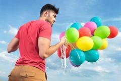 Achtermening van de toevallige mens met ballons Stock Fotografie