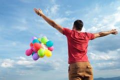 Achtermening van de toevallige mens met ballons Royalty-vrije Stock Afbeelding