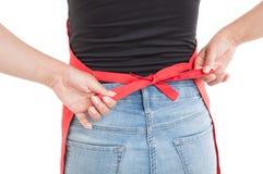 Achtermening van de vrouwelijke koorden van de werknemers bindende schort stock fotografie