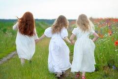 Achtermening van drie meisjes die witte kleding dragen die toge lopen Royalty-vrije Stock Foto