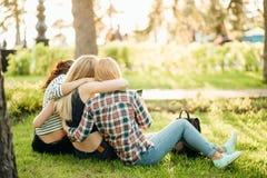 Achtermening van drie mooie vrouwen die op gras en omhelzingen zitten stock fotografie