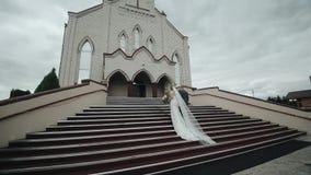 Achtermening van een bruid in een lange witte kleding en een bruidegom die boven van een mooi gebouw gaan stock video