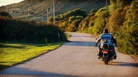 Achtermening van een fietser op een klassieke motorfiets Stock Foto