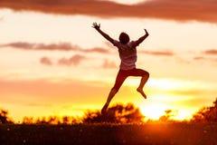 Achtermening van een Gelukkige Jongen die tegen Zonsondergang springen Stock Afbeeldingen