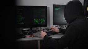 Achtermening van een hakker die met een kap cyber aanval op banknetwerk maken De mens in zwarte typt snel op toetsenbord en diefs stock videobeelden
