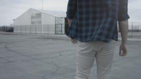 Achtermening van een het lopen kerel die een plaidoverhemd en jeans dragen Lopend op een epische manier, zeker lopen Het draaien  stock footage