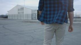 Achtermening van een het lopen kerel die een plaidoverhemd en jeans dragen Lopend op een epische manier, zeker lopen Langzame Mot stock video