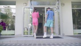Achtermening van een jong paar met raketten die sportencentrum ingaan Het meisje in roze kleren en mens in blauwe sportslijtage stock video