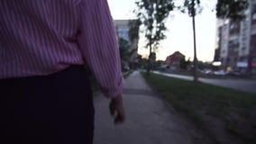 Achtermening van een jonge niet geïdentificeerde vrouw die in formele kleding langs de stoep loopt stock video