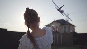 Achtermening van een leuk meisje die met het kleine stuk speelgoed vliegtuigclose-up spelen De kind het besteden tijd in openluch stock video