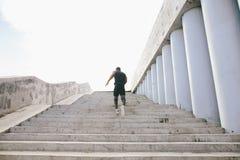 Achtermening van een mannelijke atleet het lanceren trap buiten de bouw Royalty-vrije Stock Afbeeldingen