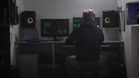 Achtermening van een mens die in zwarte kleren bij de lijst zitten De Cyberspion binnendringt in een beveiligd computersysteem la stock video