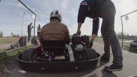 Achtermening van een mens in een auto die zich voorbereidingen treffen te bewegen Ga -gaan-kart spoorarbeider opstart de motor en stock videobeelden