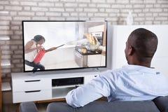 Achtermening van een Mens het Letten op Televisie royalty-vrije stock afbeeldingen