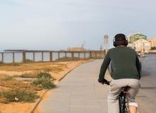 Achtermening van een mens met hoofdtelefoons die de fiets berijden door het overzees royalty-vrije stock afbeeldingen