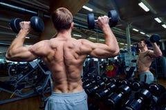 Achtermening van een sportieve mens met domoren in zijn wapens in de gymnastiek Stock Foto
