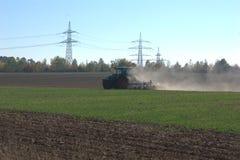 Achtermening van een tractor die een gebied ploegen en het worden de klaar winter royalty-vrije stock fotografie