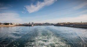 Achtermening van een veerboot die de haven verlaten stock afbeelding