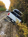 Achtermening van een vrachtwagen die de rand van een modderige weg heeft afgeslagen royalty-vrije stock foto