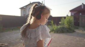 Achtermening van een vrij leuk meisje die in hoofdtelefoons de boekzitting op de portiek golvende handen lezen Het kind stock video